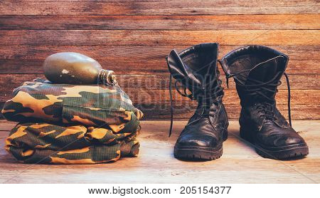old leather black men boots ankle boots military uniforms and a flask of water on wooden background front view closeup
