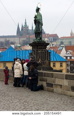 PRAGUE CZECH REPUBLIC - FEBRUARY 02 2014: Sculpture of John of Nepomuk on Charles Bridge. Beggar near tourists. The Charles Bridge is a famous historic bridge that crosses the Vltava river in Prague