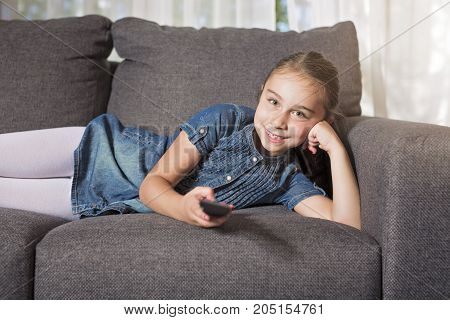 A eight years old child on a sofa at home
