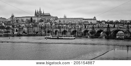 PRAGUE CZECH REPUBLIC - FEBRUARY 02 2014: View of old Prague Charles Bridge and St. Vitus Cathedral. Black and White. Stylized film. Large grains.