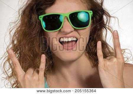 Beautiful brunette girl with curly hair and in sunglasses shows a sign that rocks and stuck out her tongue