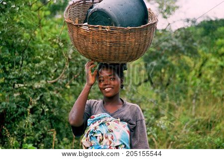 MANGUE, ANGOLA - May 15, 2007: A woman is carrying bowls and crockery on her head to their hut.