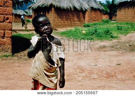 MANGUE, ANGOLA - May 15, 2007: A little boy stands with a torn shirt on a dusty road.
