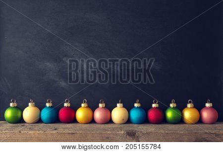 Vintage Chrsitmas baubles on a rustic wooden table with a chalkboard background