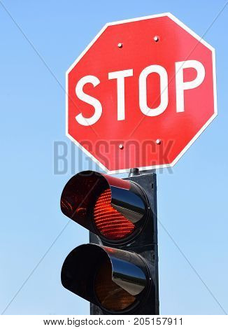 Stop sign and traffic lights at the road crossing