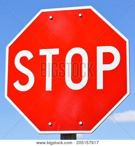 Stop sign at the road crossing closeup