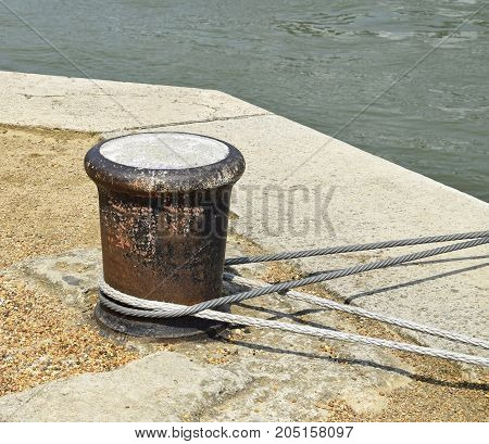Large metal bollard next to the river