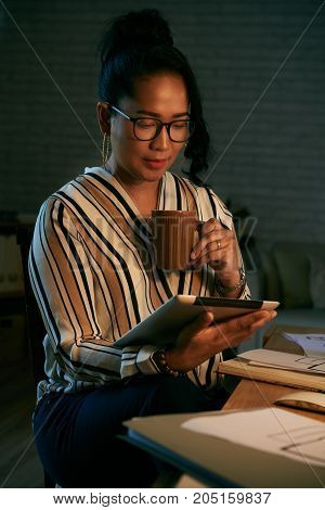 Pretty business woman drinking coffee and reading news on digital tablet