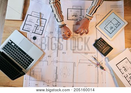 Hands of female engineer drawing blueprint, view from above