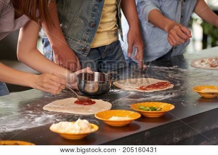 People covering pizza dough with tomato sauce