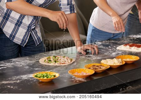 Close-up image of man putting parmesan grated cheese on pizza