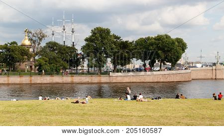 SAINT PETERSBURG, RUSSIA - AUGUST 24, 2017: People resting on the banks of the Neva river at the Peter and Paul fortress on background of Church Holy Trinity chapel and the masts of the Frigate.