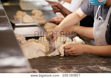 Hands of chef cutting piece of dough with scrapper knife