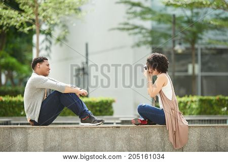 Young woman taking photo of her boyfriend outdoors