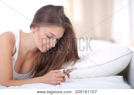 Beautiful young woman reading a text message while lying on her bed