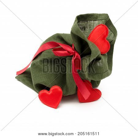 Christmas present bag with red ribbon bow and scattered red heart shape toy isolated on white background. Christmas decoration.