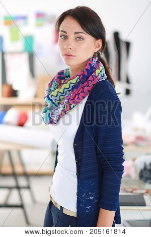 Beautiful young fashion designer standing in studio