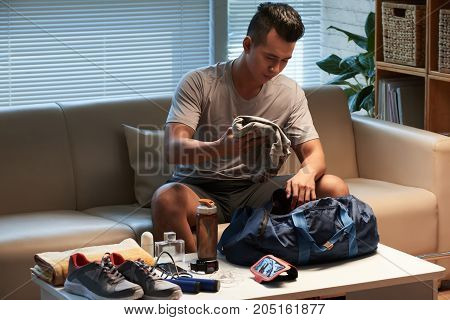 Young man putting everything for the gym into sports bag
