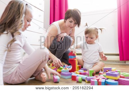 A Child girl together with mother playing educational toys