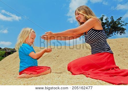 Family country plantation holidays with kids. Happy child with mother sit on heap of farm grains crop. Rice seeds sifting through woman hand fingers. Agriculture cereal plants raw food ingredients.