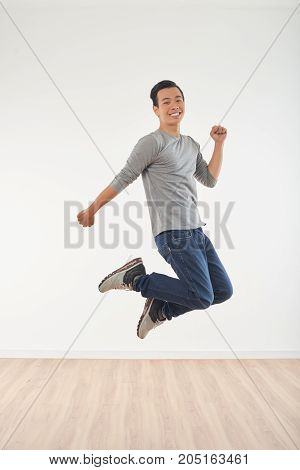Full-length portrait of young happy Asian man jumping