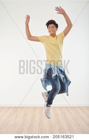 Handsome young Vietnamese man jumping of joy