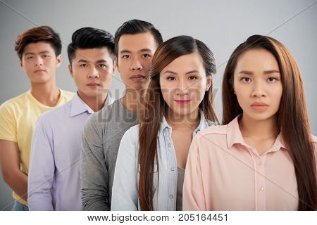 Group of unsmiling Vietnamese young people standing close to each other and looking at camera
