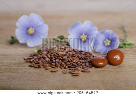 Flax Seeds , Beauty Flower And Pills On Woooden Background. Phytotherapy.