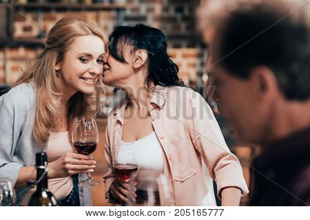 beautiful smiling middle aged women gossiping and drinking red wine