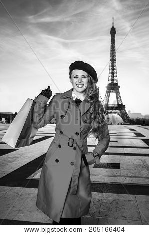 Bright in Paris. Portrait of happy young traveller woman in red coat against Eiffel tower in Paris France with shopping bag