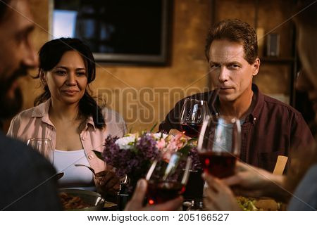 cropped shot of beautiful middle aged couple having dinner and drinking wine with friends