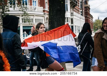 Amsterdam Netherlands - 27 April 2017: Beautiful young pretty woman with national Dutch flag. Lifestyle outdoor portrait of girl