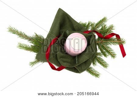 Christmas present bag with candle laying in fir tree branches isolated on white background. Christmas decoration.