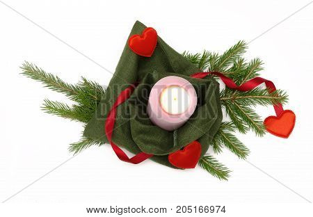 Christmas present bag with red ribbon bow with candle and red heart shape toy laying in fir tree branches isolated on white background. Christmas decoration.