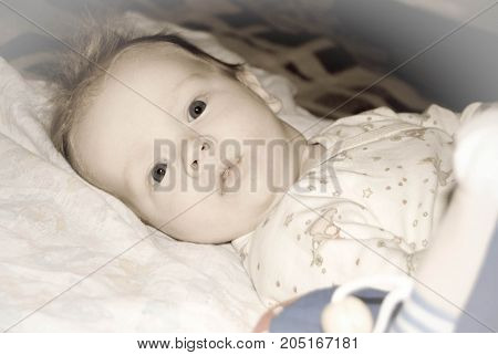 A face portrait of a baby boy at a bed looking with interest in soft yellowish colors