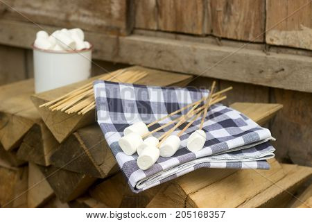 Marshmallow on wooden sticks for frying on an open fire. Rustic style, selective focus.