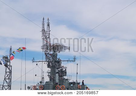Top part of big military battleship with towers masts flags of coloring and antennas