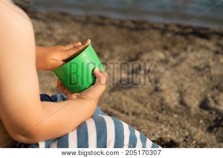 Child in striped shorts is sitting on the beach with a green mold