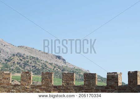 Sudak Crimea Russia June 29 2017: Old wall with battlement in Sudak fortress Crimea. Mountain on the background.