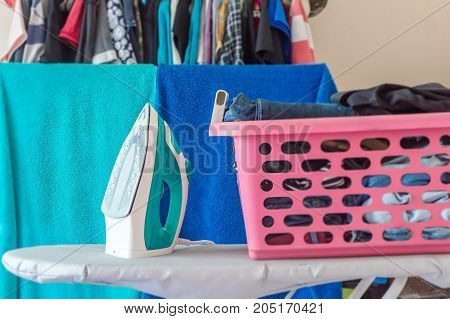 Ironing clothes on ironing boardPile of clothes in the white room.Ironing concept.