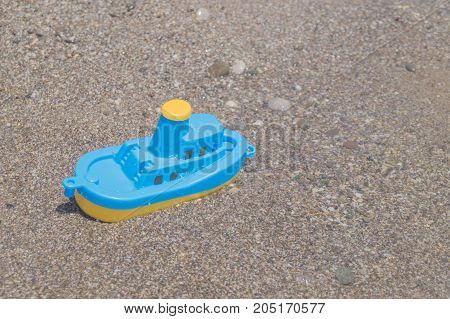 A blue-yellow toy boat on the sandy beach