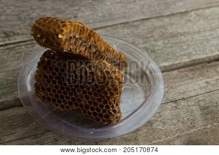 Brown honeycomb in the clear plastic dish on the old grey wooden background