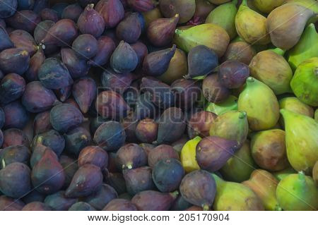 Dark blue and green figs in the market as a background
