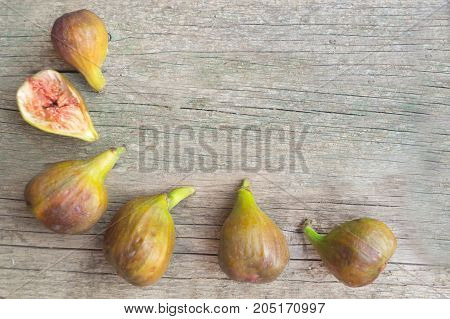 Ripe green and brown figs are arranged in the form of a frame on the wooden table