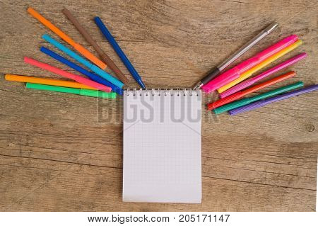 Open white notepad with colorful felt-tip pens and ball pens on the wooden table