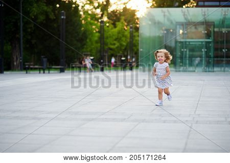 Wonderful little girl runs around the square in a city park. Warm summer day. Baby is very fun.The child stuck out his tongue from pleasure.