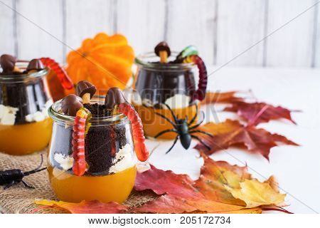 Layered halloween dessert with pumpkin jello, cream and chocolate cookies in glass jars on autumn background. Selective foucs