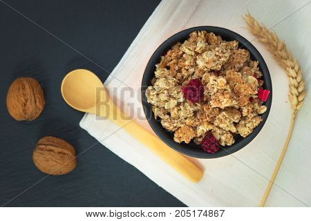 Food breakfast concept Organic Muesli or Granola and milk with napkin on black slate stone plate