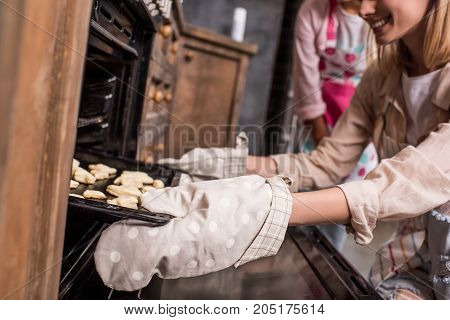 cropped shot of smiling woman putting raw cookies into oven