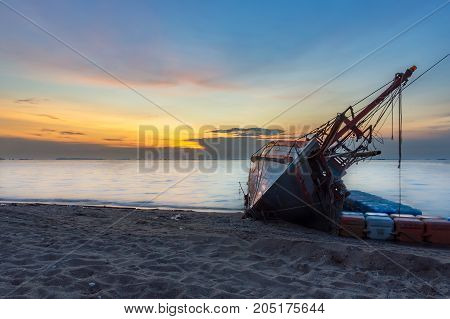 An old shipwreck or abandoned shipwreck Boat capsized on the sand beach in beautiful colorful twilight sunset background with plastic tank movement Pattaya of Thailand.